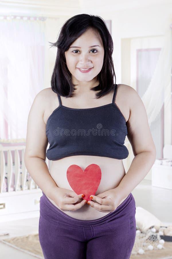 A mulher gravida guarda o símbolo do coração fotografia de stock