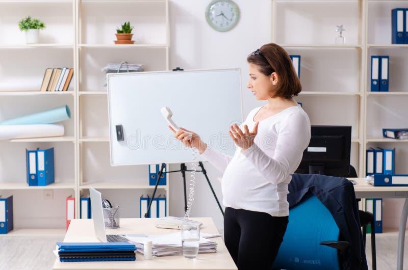 Mulher gravida idosa que trabalha no escrit?rio fotos de stock royalty free