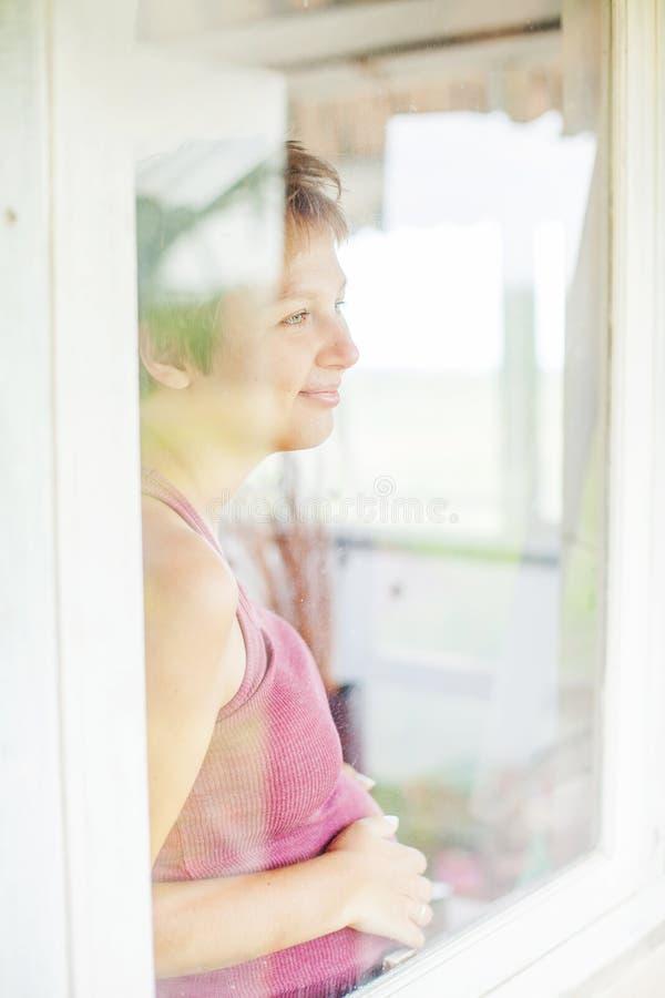 Mulher gravida a janela em casa imagens de stock royalty free