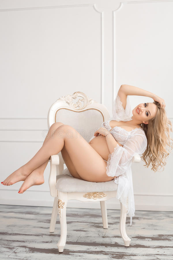 Mulher gravida loura no roupa interior branco interno na cadeira imagens de stock royalty free