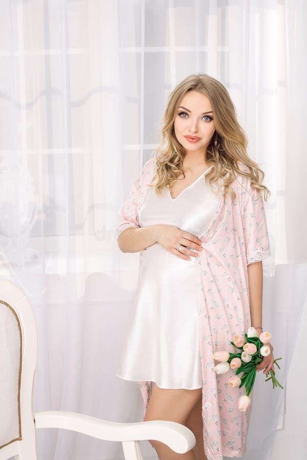 Mulher gravida loura nova atrativa que levanta na camiseta branca Menina 'sexy' do encanto feliz em casa fotografia de stock