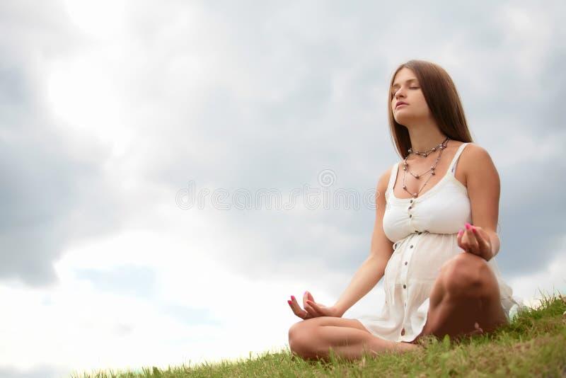 A mulher gravida meditating fotos de stock