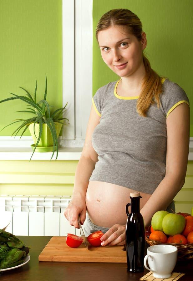 Mulher gravida na cozinha fotografia de stock royalty free