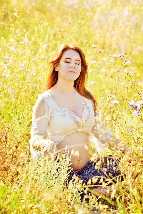 Mulher gravida na grama seca imagem de stock