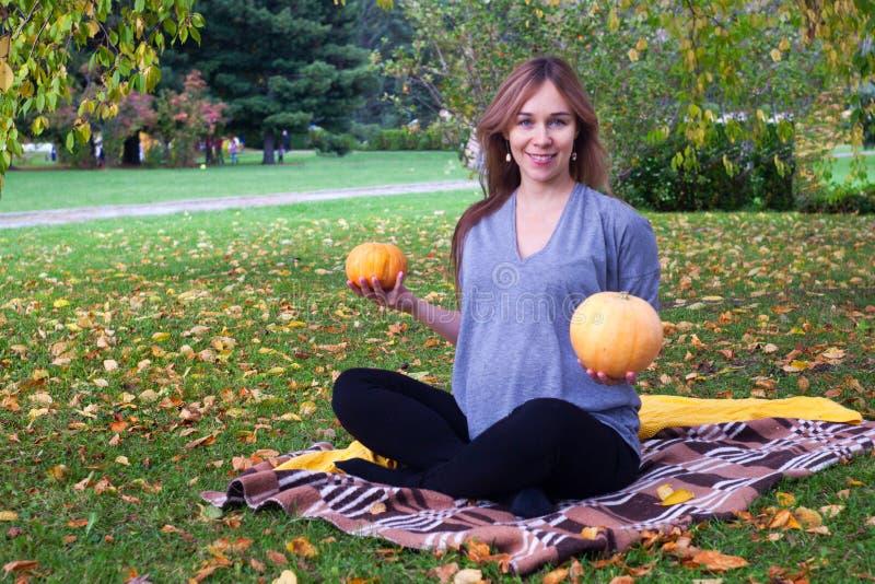 Mulher gravida na natureza que guarda duas abóboras em suas mãos, prenancy engraçado do og do conceito, tempo do outono imagem de stock royalty free