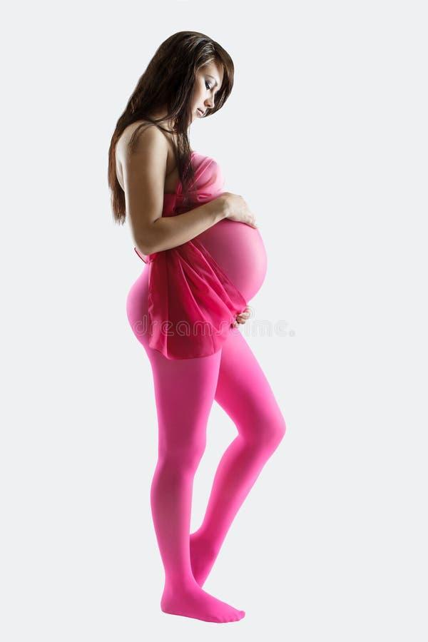Mulher gravida na proposta cor-de-rosa dos leggens que guarda sua barriga, isolada imagem de stock