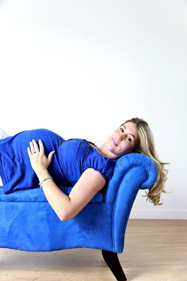 Mulher gravida no sofá fotos de stock