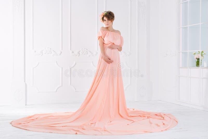Mulher gravida no vestido de noite cor-de-rosa Tiro da forma fotos de stock