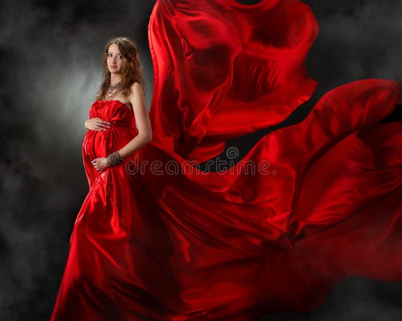 Mulher gravida no vestido vermelho do vôo fotografia de stock