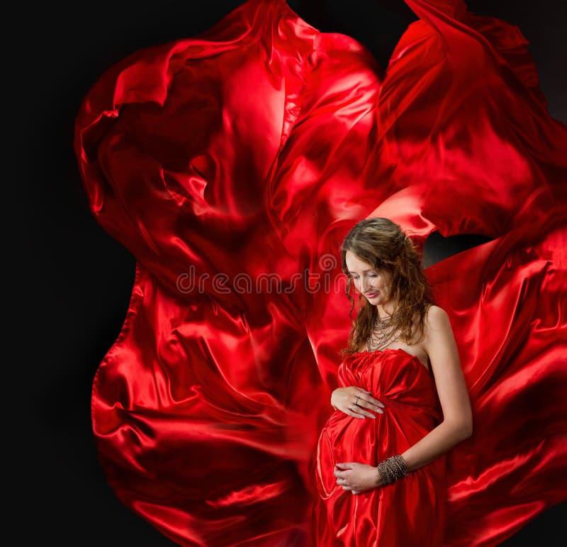 Mulher gravida no vestido vermelho do vôo imagem de stock royalty free