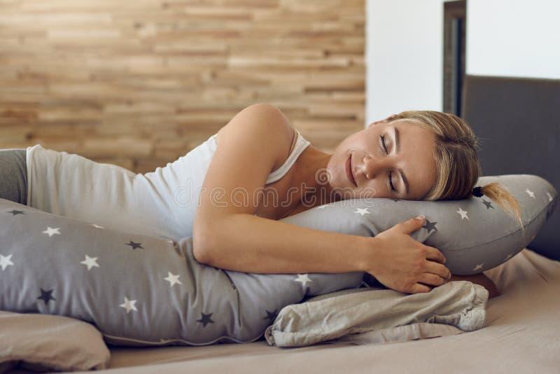 Mulher gravida nova bonita que dorme usando um coxim do apoio especial imagens de stock royalty free