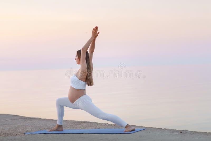 Mulher gravida nova bonita que faz o exercício da ioga ou da aptidão, pose dos lótus na esteira azul da ioga em casa Feliz e fotos de stock royalty free