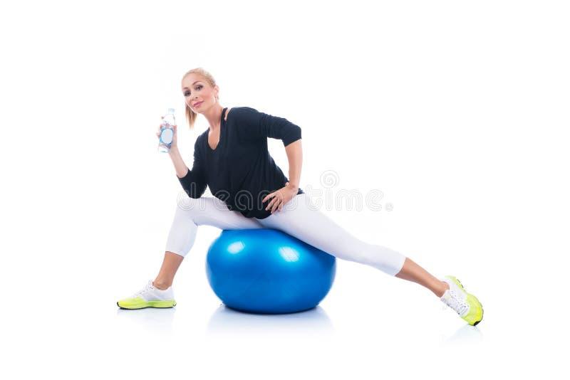 Mulher gravida nova bonita que levanta com a bola azul dos pilates em um fundo branco Gravidez adiantada imagens de stock royalty free