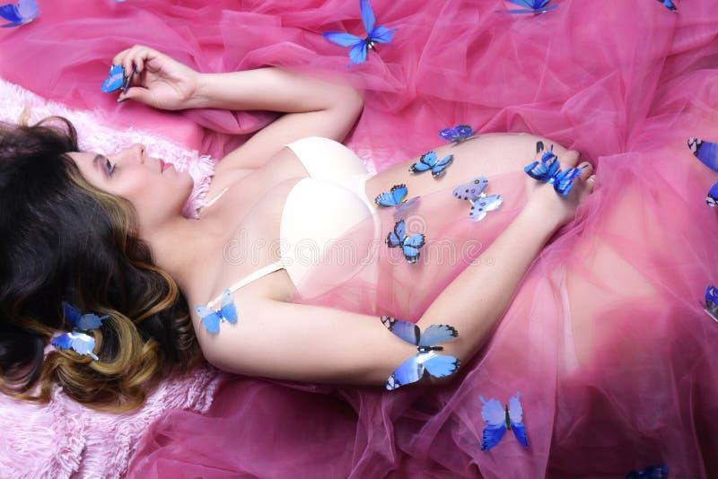 Mulher gravida nova com as borboletas em seu corpo que encontra-se no p fotos de stock