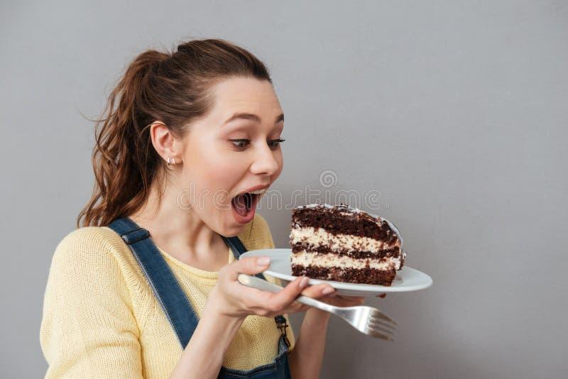 Mulher gravida nova com fome que vai comer o bolo de chocolate fotografia de stock royalty free