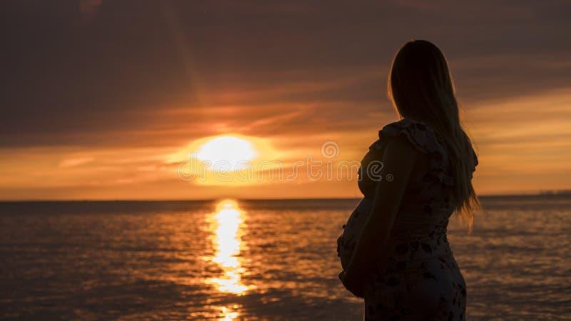 A mulher gravida nova com uma barriga grande olha o por do sol majestoso sobre o mar Em antecipa??o a uma crian?a foto de stock royalty free