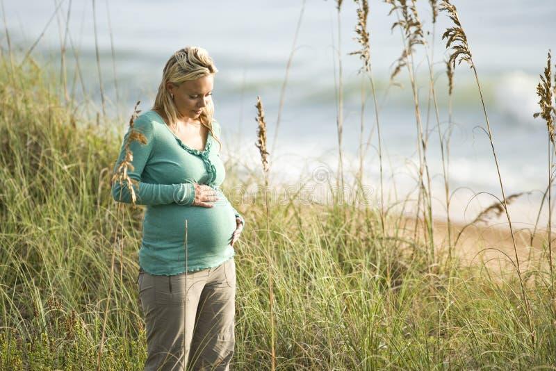 Mulher gravida nova contemplativa na praia imagem de stock royalty free