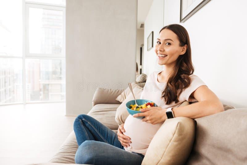 Mulher gravida nova de sorriso que come o café da manhã saudável foto de stock royalty free