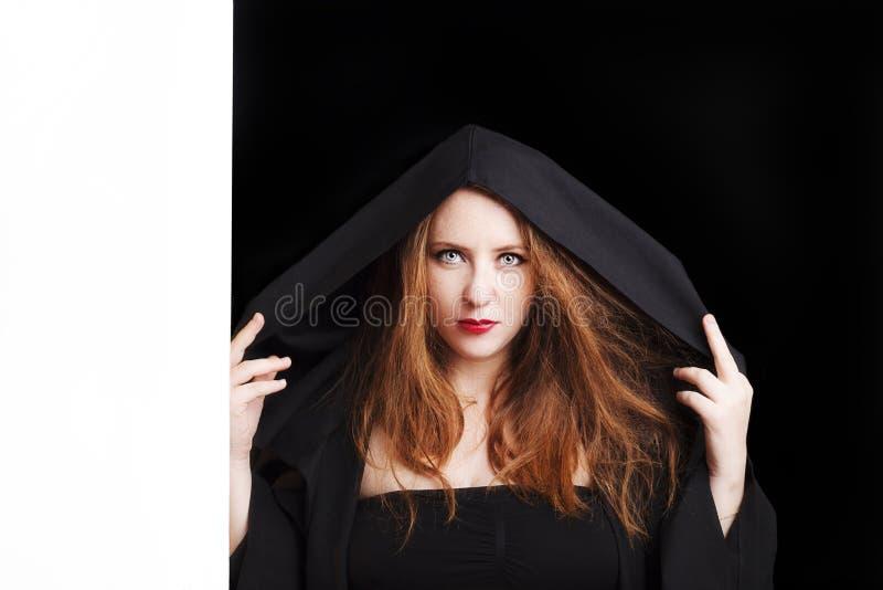 Mulher gravida nova do ruivo bonito em um casaco preto com uma capa fotografia de stock