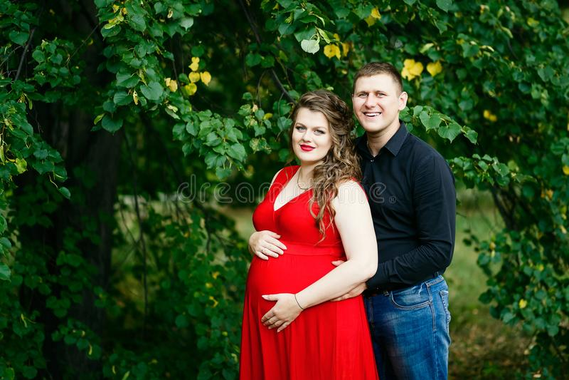 Mulher gravida nova e seu abraço do marido no parque verde imagem de stock royalty free