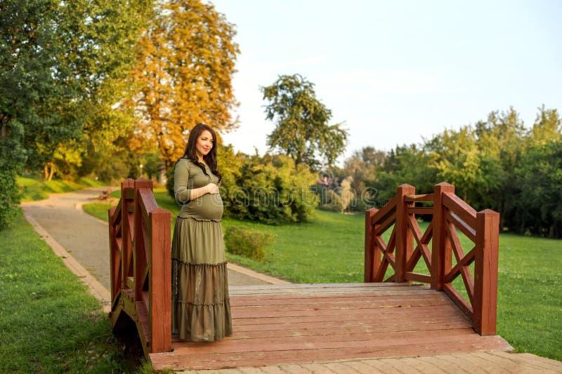 A mulher gravida nova em antecipação a um bebê que está em um parque no sol irradia fotos de stock royalty free