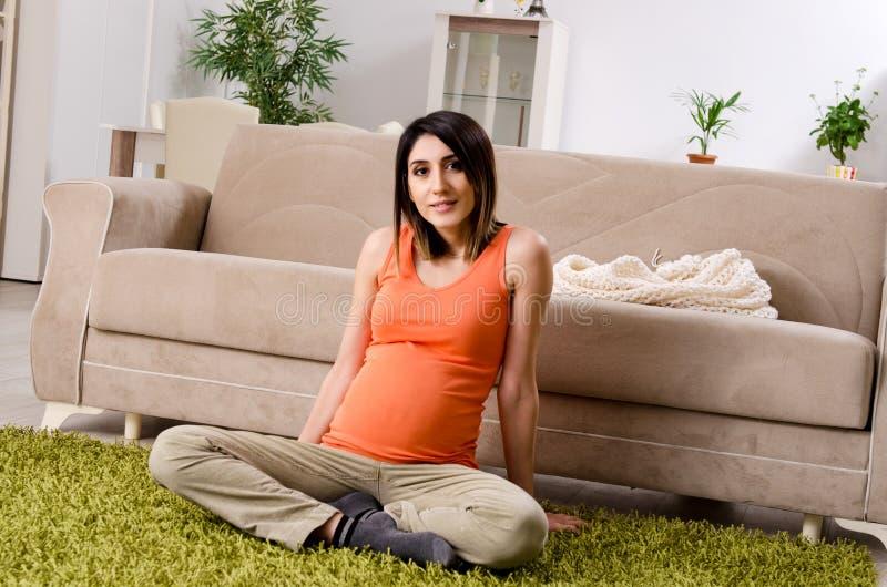 A mulher gravida nova em casa imagens de stock