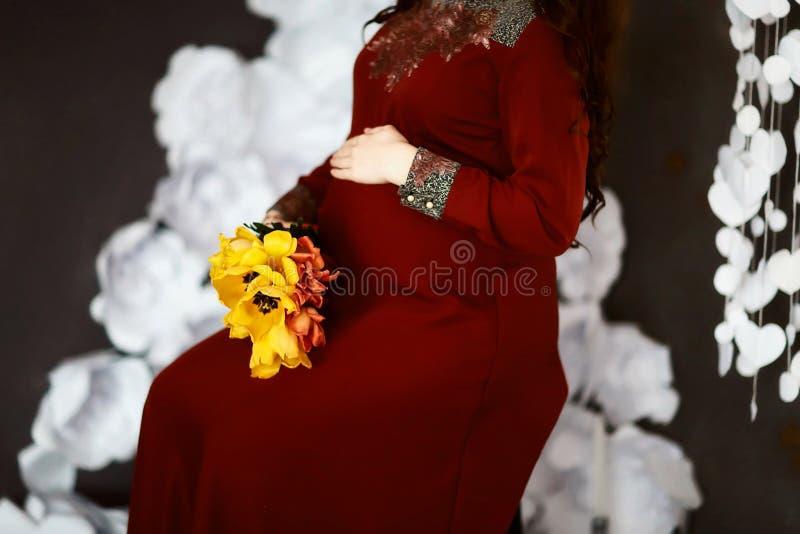 A mulher gravida nova em um vestido vermelho guarda suas mãos em sua barriga inchada com as flores da mola de tulipas amarelas, c fotos de stock royalty free