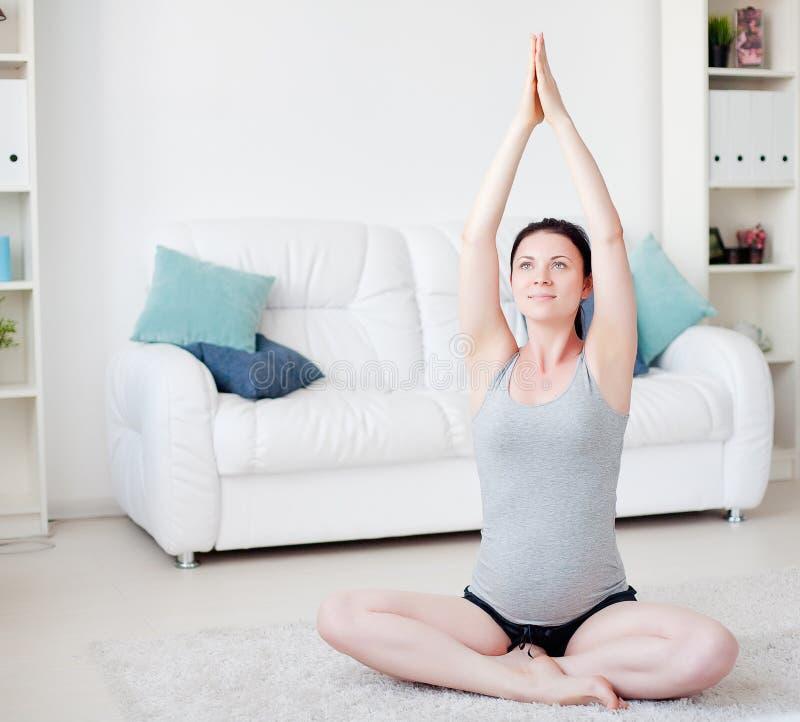 A mulher gravida nova faz a ioga imagem de stock royalty free