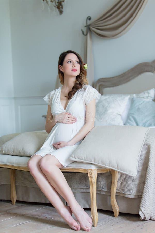 Mulher gravida nova no assento branco do vestido foto de stock royalty free