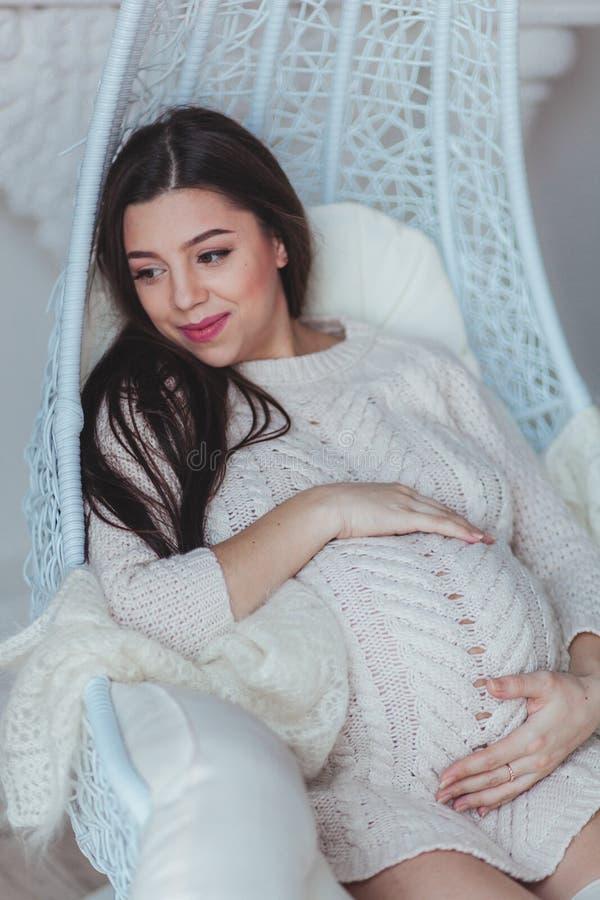 A mulher gravida nova no branco fez malha a camiseta que senta-se na poltrona em casa e que toca em sua barriga Gravidez e imagem de stock