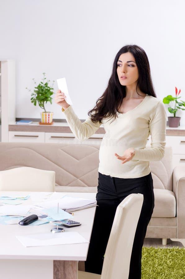 Mulher gravida nova no conceito do planeamento do or?amento fotografia de stock royalty free