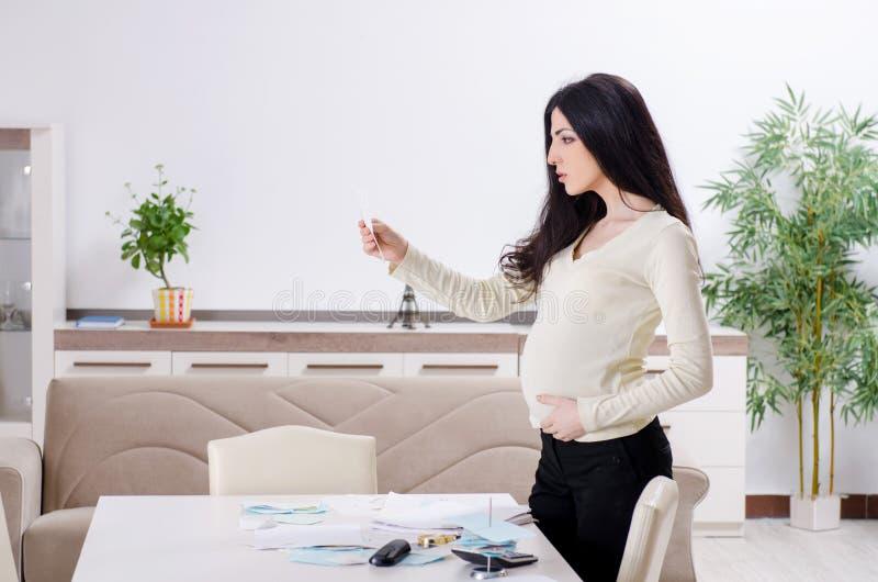 Mulher gravida nova no conceito do planeamento do or?amento imagem de stock royalty free