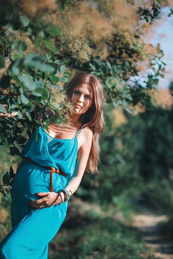 Mulher gravida nova no parque fora Mulher gravida calma no terceiro trimestre Andando em público o jardim imagens de stock royalty free