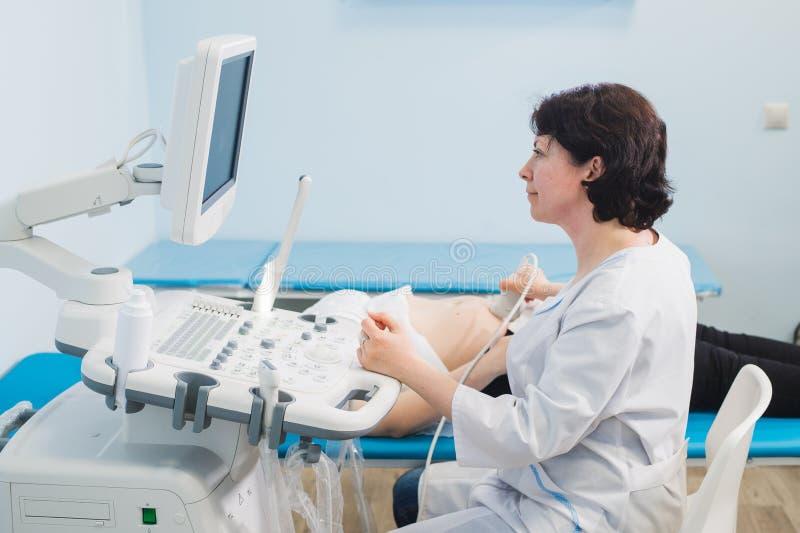 Mulher gravida nova no ultrassom, exame médico completo com o doutor fotos de stock royalty free