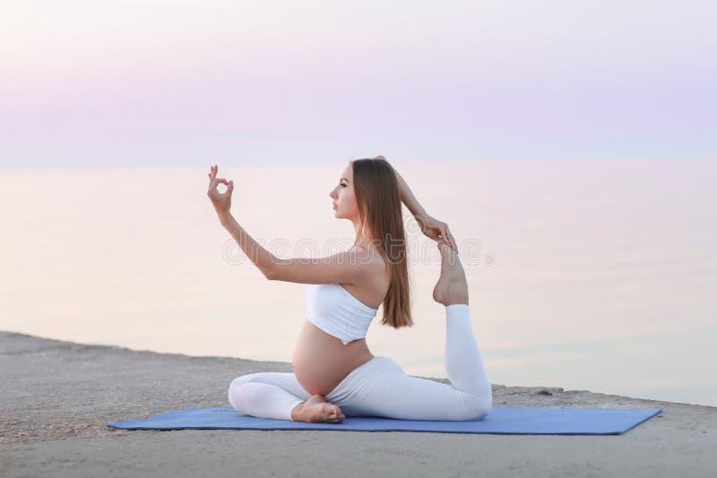 Mulher gravida nova no vestido branco que senta-se na praia perto do mar azul e que respira Férias de verão durante a gravidez imagens de stock royalty free