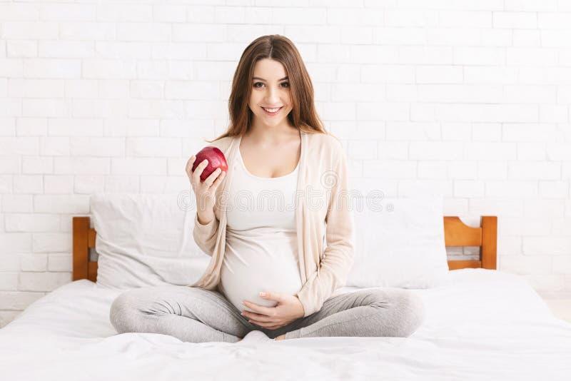Mulher gravida nova que come a maçã na cama em casa fotos de stock