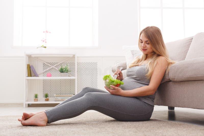 Mulher gravida nova que come a salada verde fresca fotografia de stock royalty free