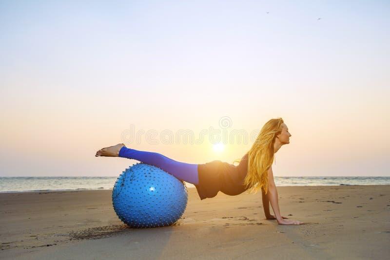 Mulher gravida nova que estica na bola de formação contra o por do sol sobre o mar Beleza e saúde durante a gravidez Ioga, Pilate imagens de stock