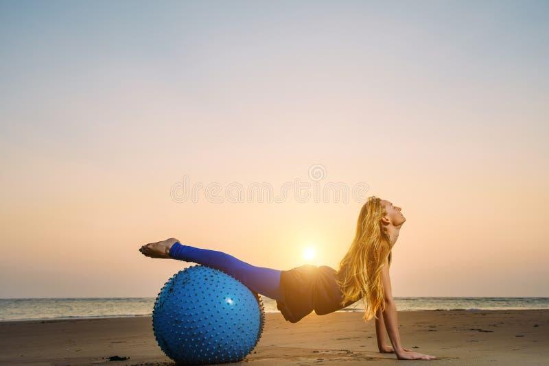 Mulher gravida nova que estica na bola de formação contra o por do sol sobre o mar Beleza e saúde durante a gravidez Ioga, Pilate foto de stock royalty free
