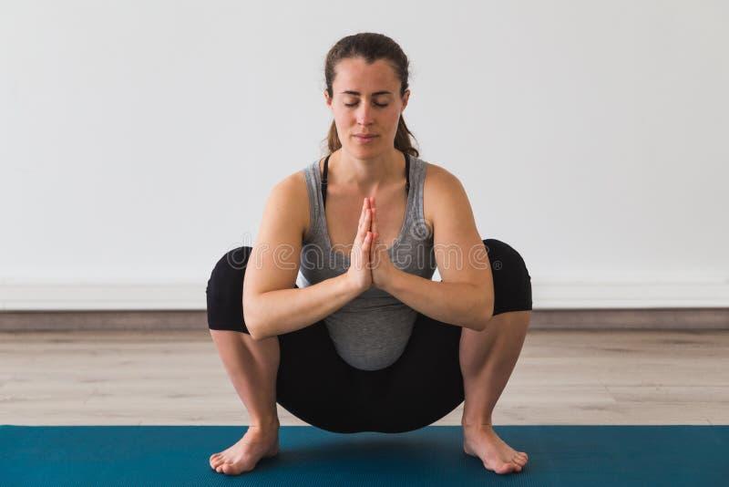 Mulher gravida nova que faz a pose pré-natal da ioga com mãos do namaste fotografia de stock