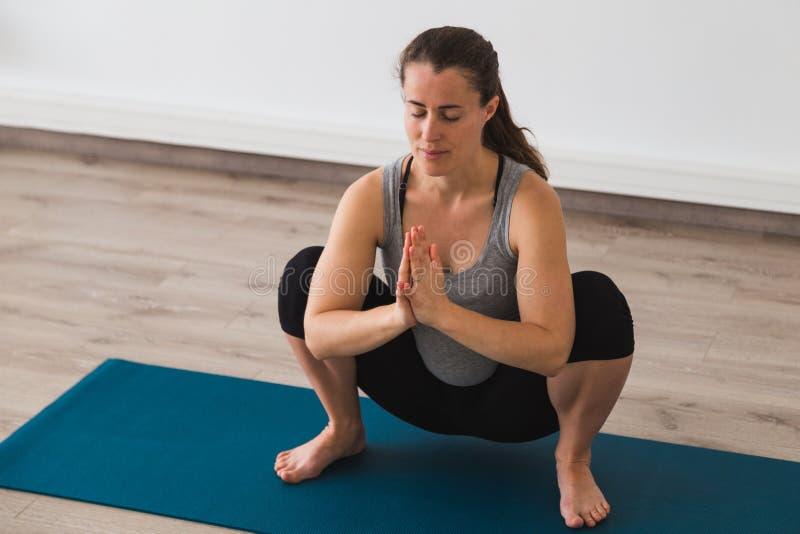 Mulher gravida nova que faz a postura pré-natal da ioga com mãos do namaste imagens de stock