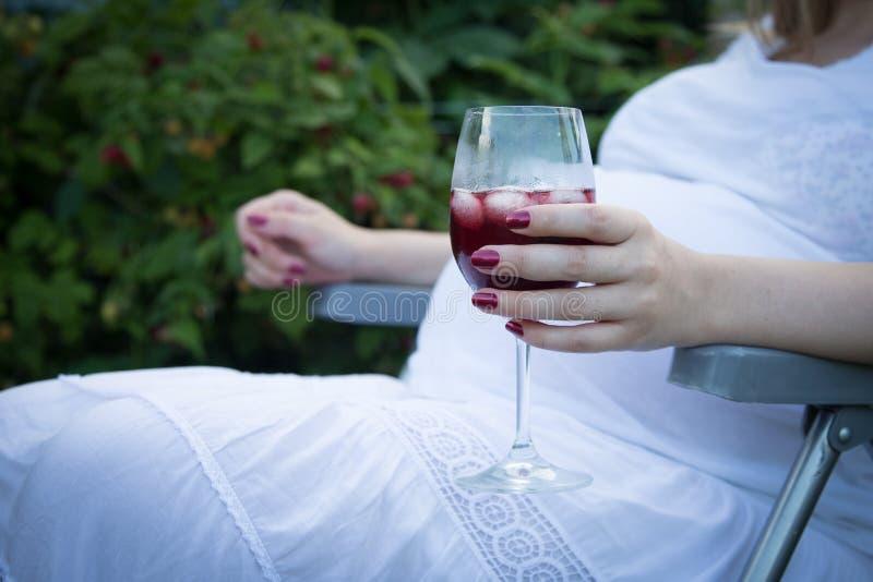 Mulher gravida nova que guarda o vinho e o cigarro fotos de stock royalty free