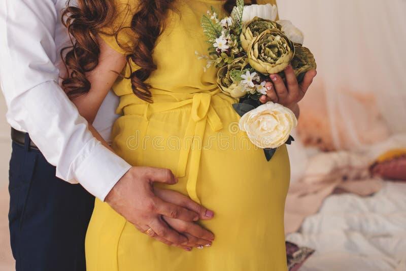 Mulher gravida nova que guarda sua barriga sobre a janela branca com a bandeira do espaço da cópia imagem de stock