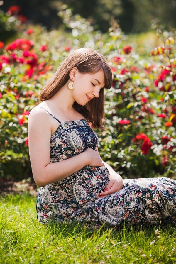 Mulher gravida nova que relaxa no parque fora fotografia de stock royalty free