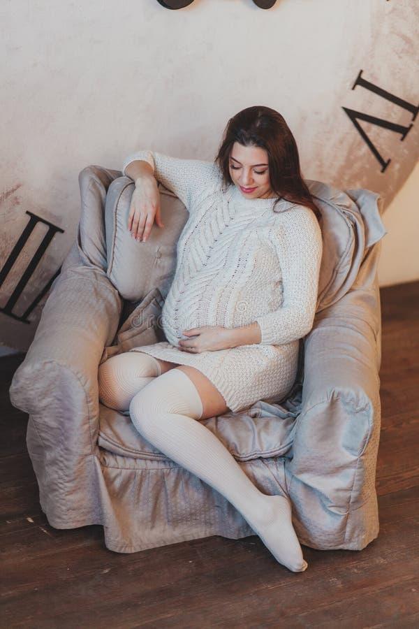 Mulher gravida nova que senta-se na poltrona com o pulso de disparo grande no fundo da parede Tempo de espera em que o bebê conce fotos de stock royalty free