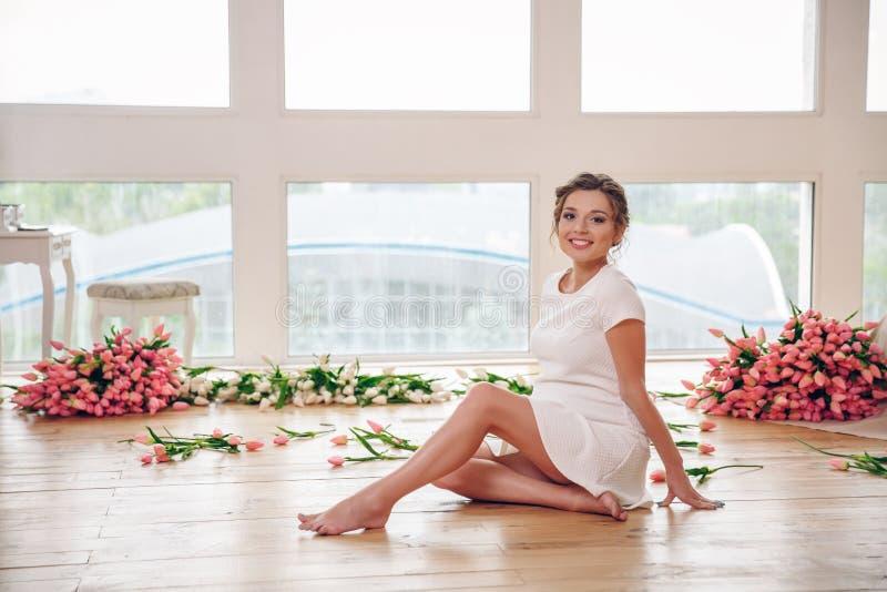 Mulher gravida nova que senta-se no assoalho perto das janelas em casa fotos de stock royalty free