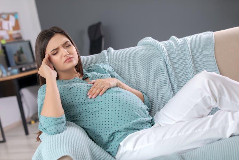 Mulher gravida nova que sofre da dor de cabeça fotos de stock