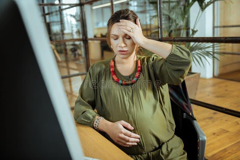 Mulher gravida nova que tem a dor de cabeça após o trabalho no computador imagem de stock
