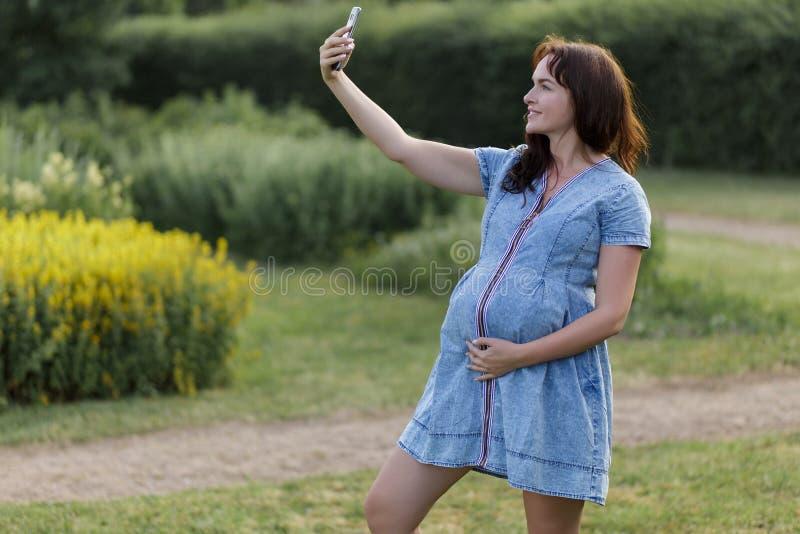 Mulher gravida nova que toma um selfie no parque foto de stock