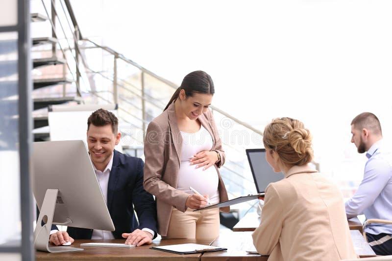Mulher gravida nova que trabalha com seus empregados fotografia de stock